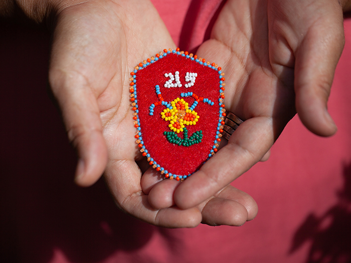 Deborah Young holds a red vamp beaded with the number 215 and a flower